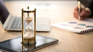 Time is running in hourglass, female manager checking graphs at office desk, stock footage